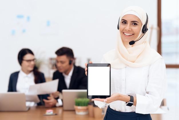 De vrouw in de hijab staat in het callcenter.