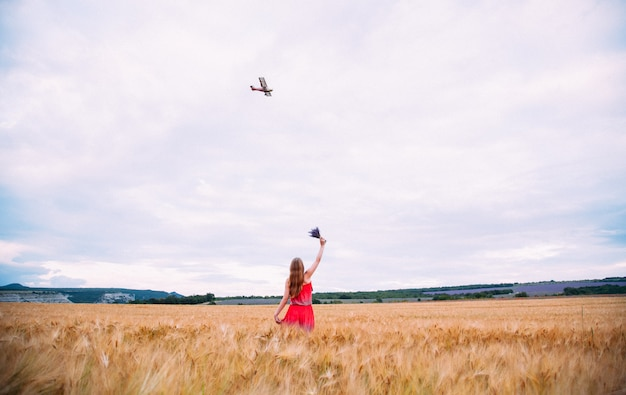 De vrouw in de rode jurk op tarweveld zwaaien naar het vliegtuig.