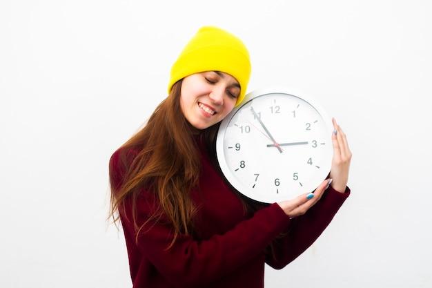 De vrouw in een gele hoed glimlacht op een witte achtergrond en koestert ac-slot met gesloten ogen