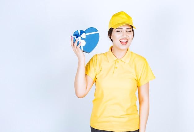 De vrouw in een gele, ongevormde doos in de vorm van een hart
