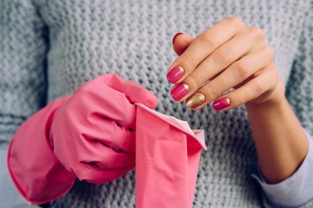 De vrouw in een grijze sweater kleedt roze rubberhandschoenen voor het schoonmaken