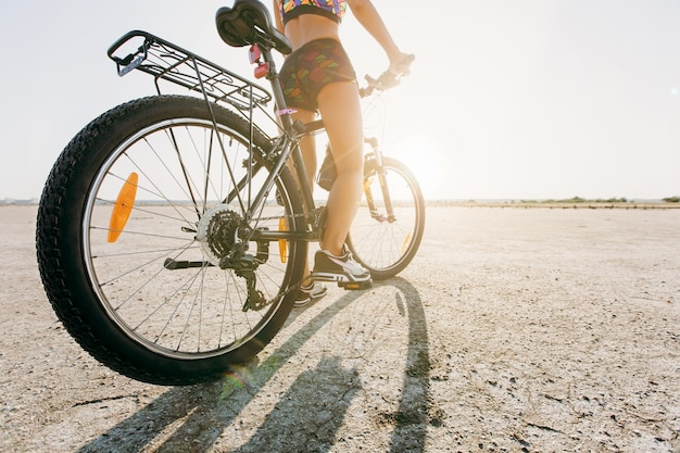 De vrouw in een veelkleurig pak zit op een fiets in een woestijngebied. geschiktheidsconcept. achteraanzicht en onderaanzicht. detailopname