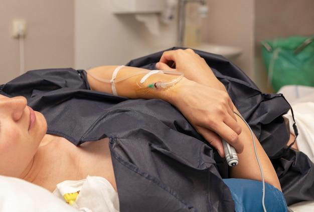 De vrouw in een verloskamer met een druppelaar en drukt op de knop van de afstandsbediening voor een regelmatige dosis epidurale anesthesie