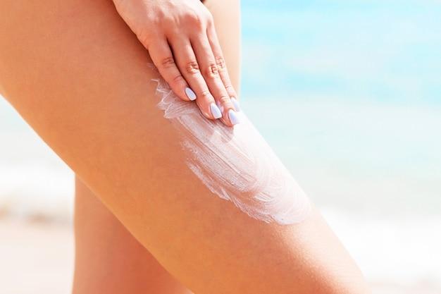 De vrouw in een zwart zwempak past zonbescherming met haar vingers op haar been bij het strand toe