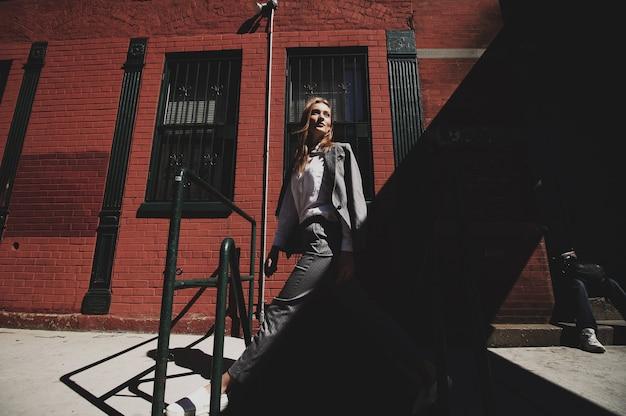 De vrouw in grijs kostuum geniet van wind op de straat van de stad van new york