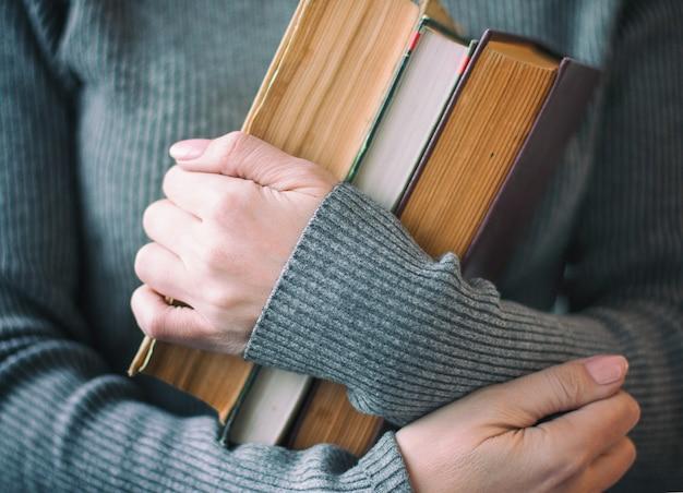 De vrouw in grijze kleren houdt oude boeken in de hand