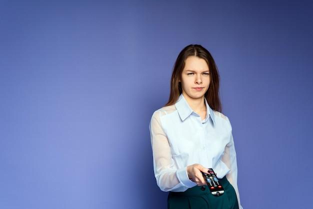 De vrouw in het blauwe shirt is teleurgesteld en moe van het nieuws op televisie. mooi meisje in de studio op een lila achtergrond schakelt kanalen met behulp van een afstandsbediening