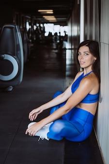 De vrouw in het comfortabele sporten rusten leunde tegen muur, gebeëindigd trainingmeisje verzamelt energieconcept