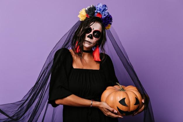 De vrouw in het kostuum van de zwarte bruid houdt pompoen vast. portret van meisje met bloemen in haar haar op lila muur.