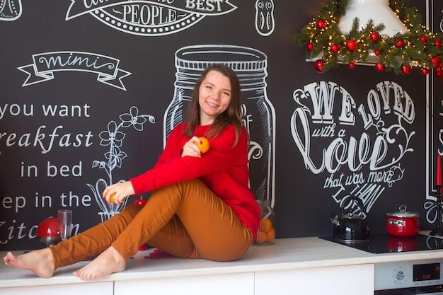 De vrouw in het rood zit in de keuken en bereidt het kerstdiner voor.