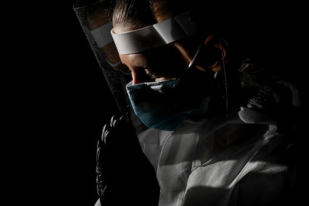 De vrouw in medische beschermende kleding bevindt zich stelt van gebed.