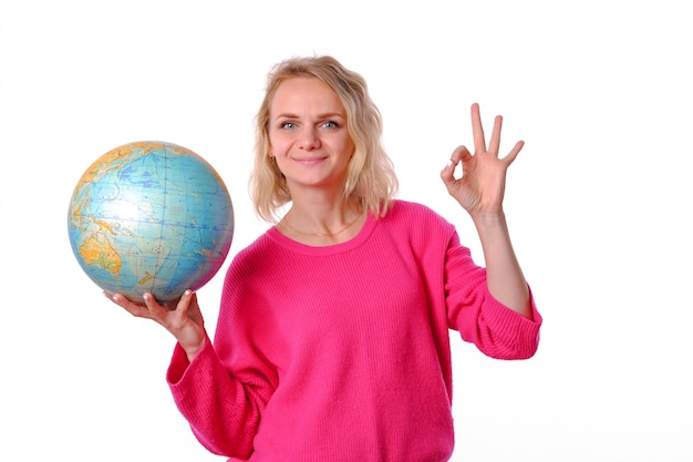 De vrouw in roze sweater toont ok ok en houdt grote bol in haar hand
