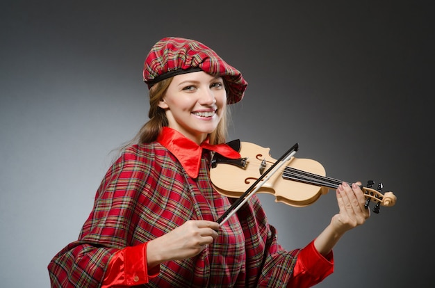 De vrouw in schotse kleding in muzikaal concept