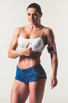 De vrouw in sportkleding en oortelefoons toont ok teken