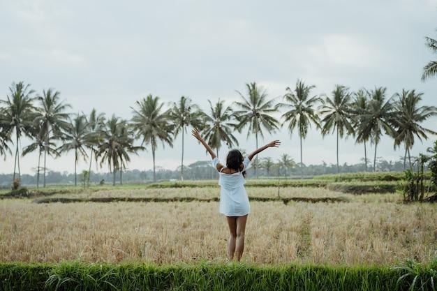 De vrouw in wit geniet van op padieveldterras