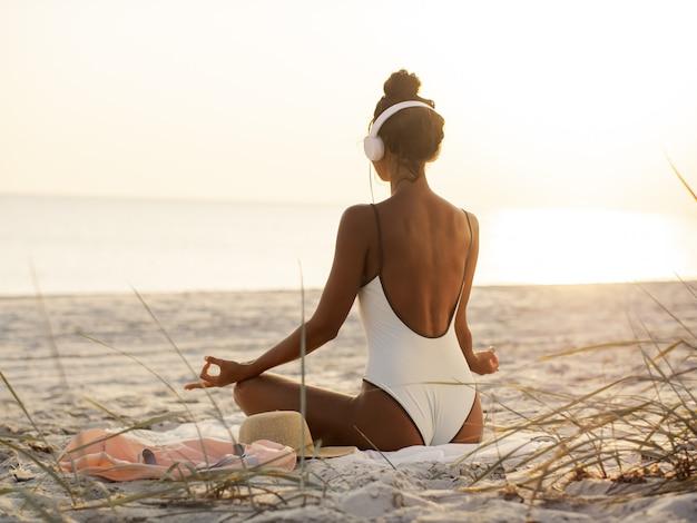 De vrouw in yogameditatie stelt met hoofdtelefoons op het strand