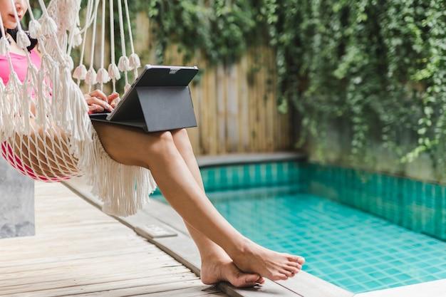 De vrouw in zwemmend kostuum zit in hangmat die aan laptop werkt bij zwembad.