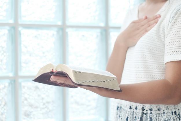 De vrouw is de bijbel aan het lezen.
