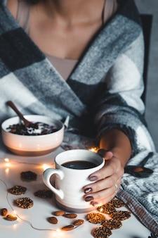 De vrouw is gewikkeld in een deken en heeft een kopje koffie in haar handen. wintercomfort, slingers, kerstsfeer.