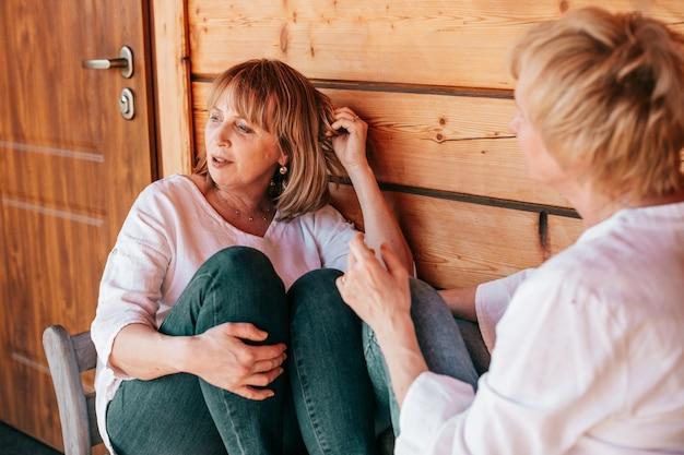 De vrouw is in gedachten verzonken en kijkt opzij terwijl haar vriendin, van achteren gezien, haar mening uitspreekt