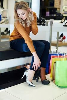 De vrouw kan niet beslissen welke schoenen ze moet kopen