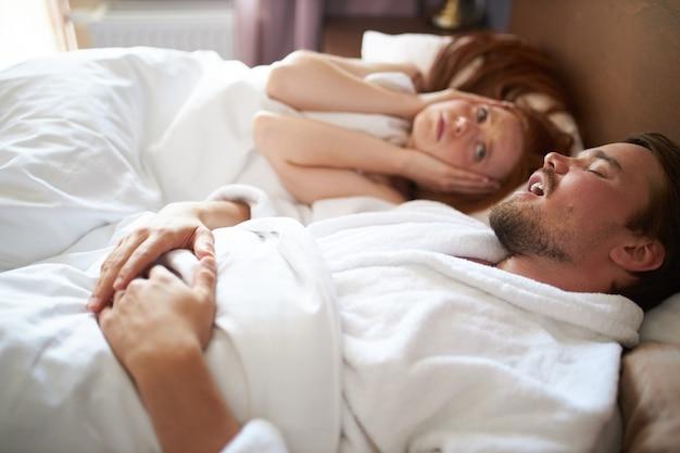 De vrouw kan niet slapen terwijl een man snurkt, ze sluit de oren en kijkt hem aan