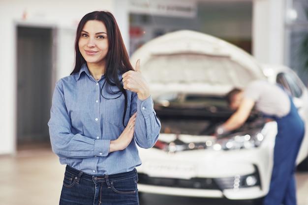 De vrouw keurt het werk van de klant goed. de monteur werkt onder de motorkap van de auto
