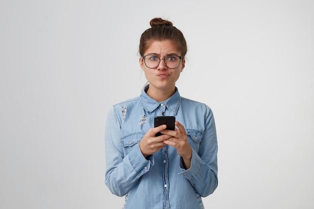 De vrouw kijkt met ongenoegen naar de camera, opgeblazen lippen, teleurgesteld, houdt smartphone in handen