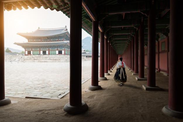 De vrouw kleedde hanbok in traditionele kleding die in gyeongbokgung-paleis in seoel, zuiden lopen