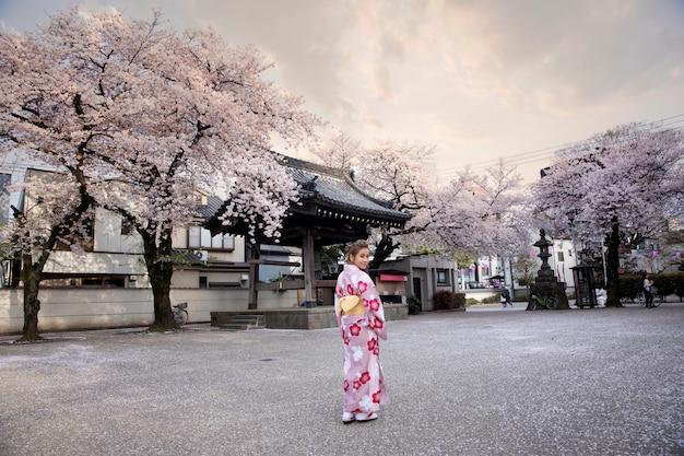 De vrouw kleedde zich in traditioneel japans kostuum bij het heiligdom fushimi-inari, kyoto japan