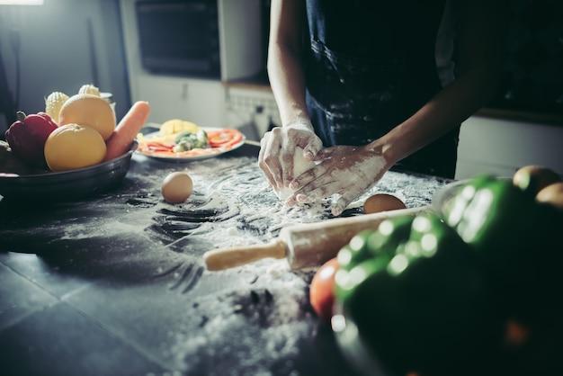 De vrouw kneedt deeg voor maakt pizza op houten. koken concept.