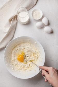 De vrouw kneedt het deeg in kom met roomkaas en ei. ingrediënten voor het koken van baskische spaanse gebrande sint-sebastiaan-cheesecake. roomkaas, suiker, eieren, bloem en room. recept stap voor stap.