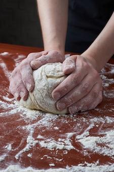 De vrouw kneedt het deeg met haar handen. vrouwelijke handen en rauw deeg op een houten achtergrond. pizzadeeg of gebak. brood, pizza, pasta bakken.