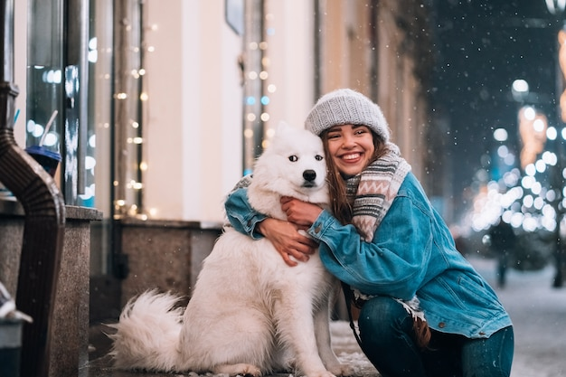 De vrouw koestert haar hond op een nachtstraat