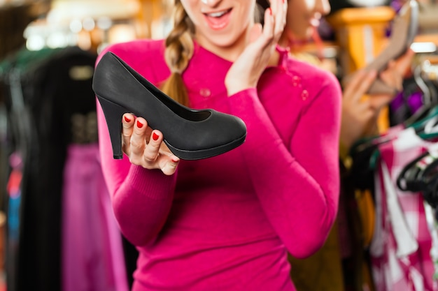 De vrouw koopt schoenen voor haar tracht of dirndl in een winkel