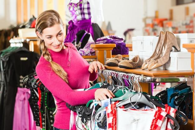 De vrouw koopt tracht of dirndl in een winkel