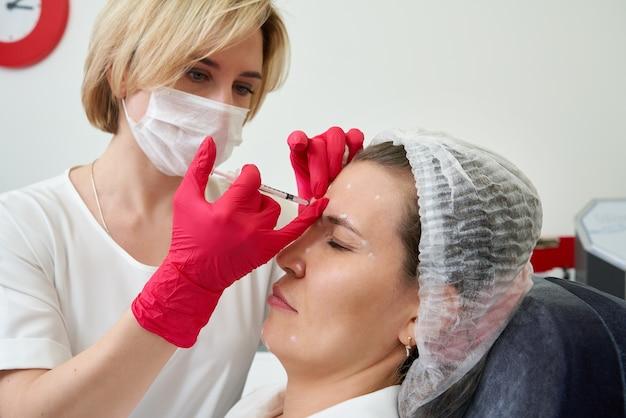 De vrouw krijgt verjongende gezichtsinjecties. de deskundige schoonheidsspecialiste vult vrouwelijke rimpels op