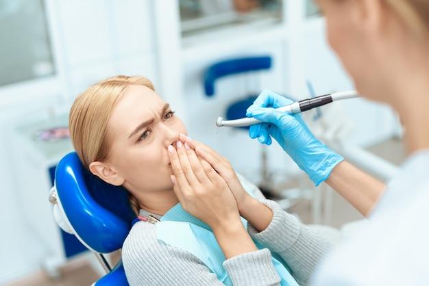 De vrouw kwam naar de tandarts. de vrouw is bang