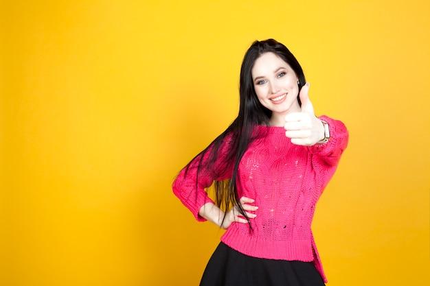 De vrouw laat zien, strekt haar hand naar voren en steekt haar duim op, op een felgele achtergrond. het concept van ondersteunende keuze en instemming, een positieve houding.