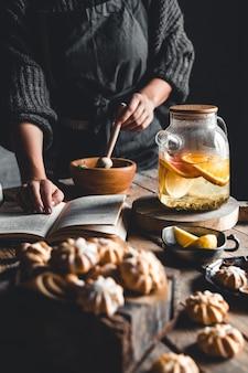 De vrouw leest en hete thee met verse grapefruit op houten tablet