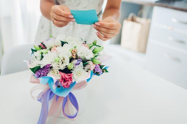 De vrouw leest kaart links in boeket van bloemen door vriend in giftdoos op keuken thuis. verrassing aanwezig