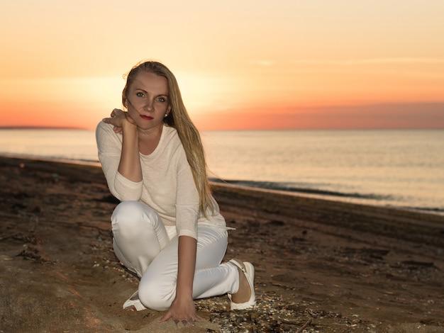 De vrouw liet de hand in het zand op de kust zakken.