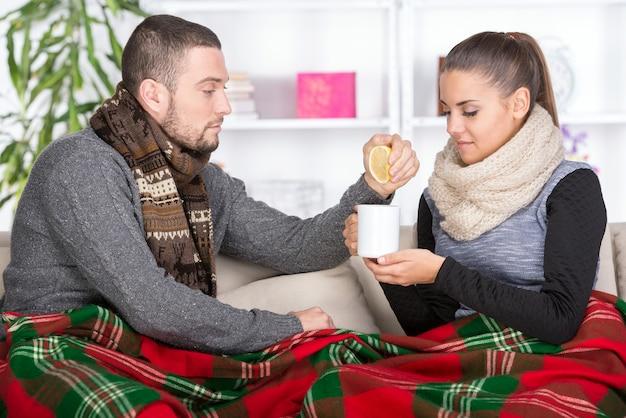 De vrouw lijdt aan koude terwijl de jongen thee bracht.