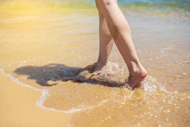De vrouw loopt blootvoets in het zand dat door overzeese golf wordt gewassen