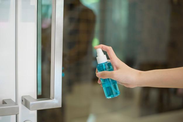 De vrouw maakt deurhandvat met alcoholnevel schoon