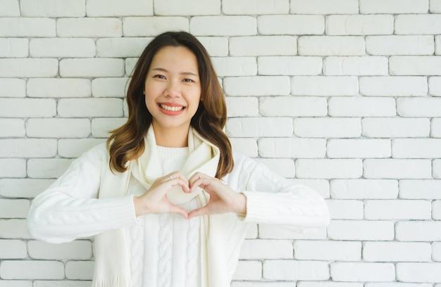 De vrouw maakt het gebaar van de hartvorm voor valentijnskaartdag of gezond levensstijlconcept
