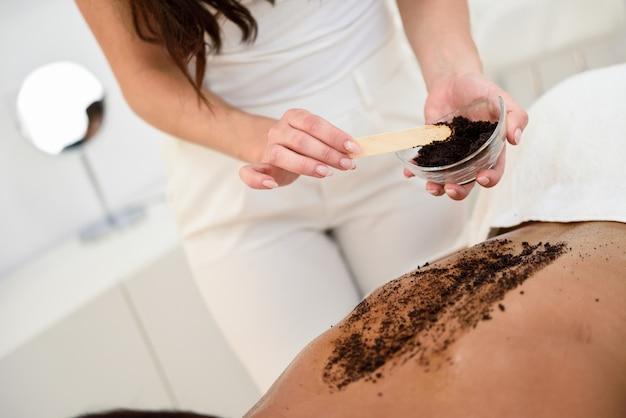 De vrouw maakt huid van het lichaam met koffiescrub schoon in kuuroordwellnesscentrum.
