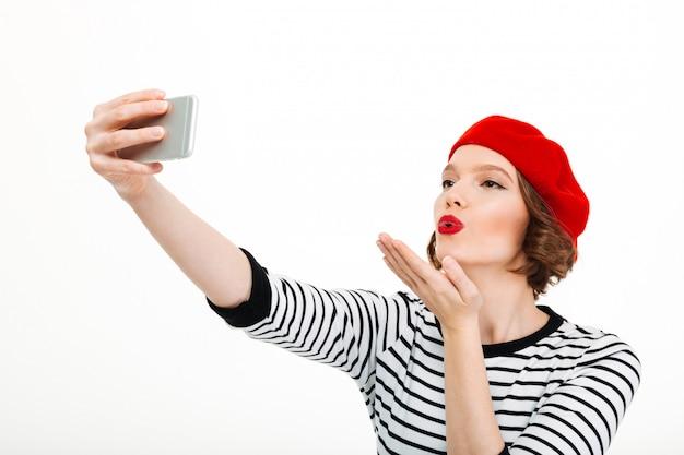 De vrouw maakt selfie door mobiele telefoon blazende kussen.