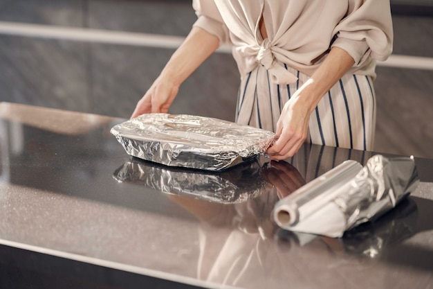 De vrouw maakt thuis een diner in de keuken