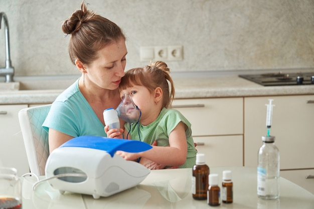 De vrouw maakt thuis inademing aan een kind. brengt het vernevelaarmasker naar zijn gezicht. inhaleert de damp van het medicijn. het meisje ademt door het masker. geneeskunde op tafel.